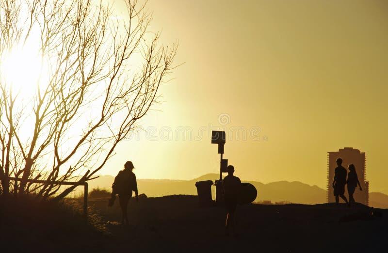 Σκιαγραφία των διαφορετικών ανθρώπων που περπατούν τη διαδρομή παραλιών στοκ φωτογραφίες