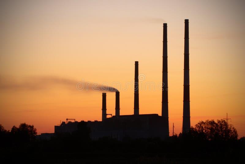 Σκιαγραφία των εγκαταστάσεων ηλεκτρικής δύναμης στροβίλων αερίου ενάντια στον ουρανό ηλιοβασιλέματος στοκ φωτογραφία