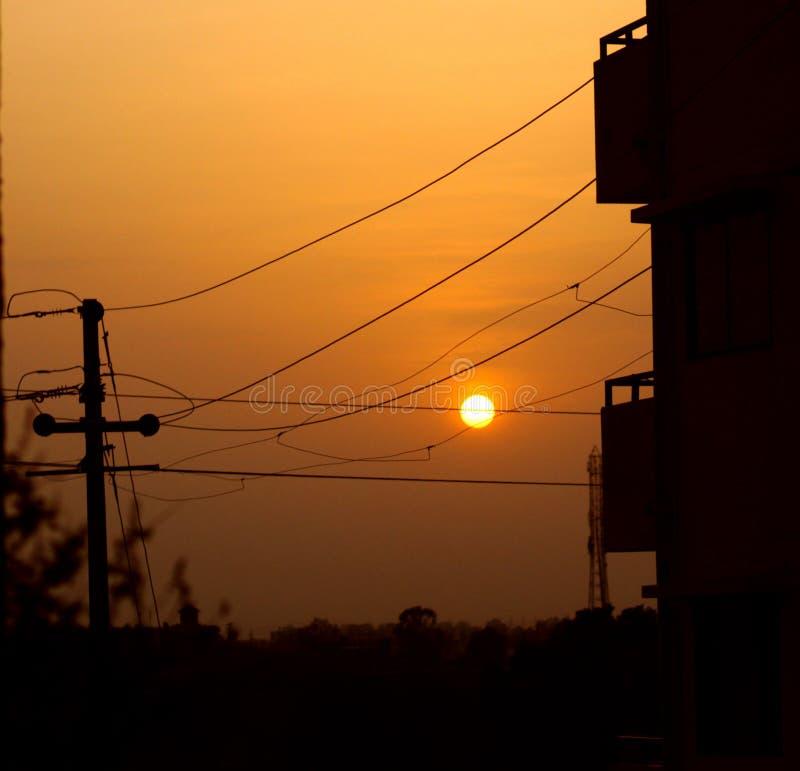Σκιαγραφία των ηλεκτρικών πόλων και των καλωδίων και του όμορφου χρυσού ήλιου στοκ εικόνες