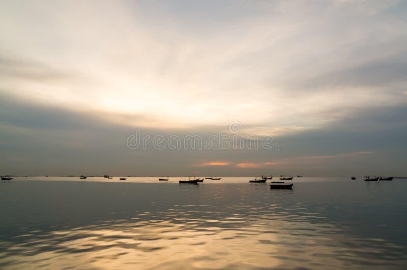 Σκιαγραφία των μικρών αλιευτικών σκαφών στη θάλασσα κατά τη διάρκεια του ηλιοβασιλέματος στοκ εικόνα με δικαίωμα ελεύθερης χρήσης