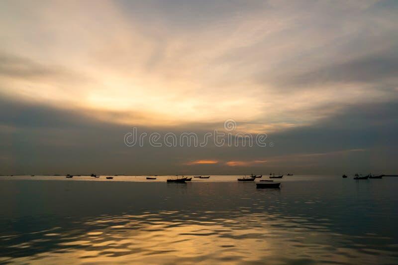 Σκιαγραφία των μικρών αλιευτικών σκαφών στη θάλασσα κατά τη διάρκεια του ηλιοβασιλέματος στοκ εικόνα