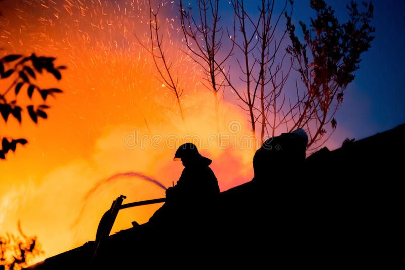 Σκιαγραφία των πυροσβεστών στη στέγη ενός καίγοντας σπιτιού στοκ εικόνες με δικαίωμα ελεύθερης χρήσης