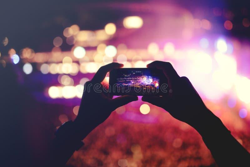 Σκιαγραφία των χεριών που καταγράφουν τα βίντεο στη συναυλία μουσικής Συναυλία μουσική ποπ με τα φω'τα, καπνός στοκ εικόνα με δικαίωμα ελεύθερης χρήσης