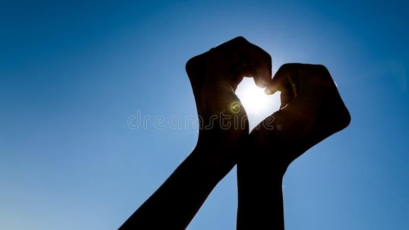 Σκιαγραφία χεριών κοριτσιών στη μορφή καρδιών στοκ φωτογραφία με δικαίωμα ελεύθερης χρήσης
