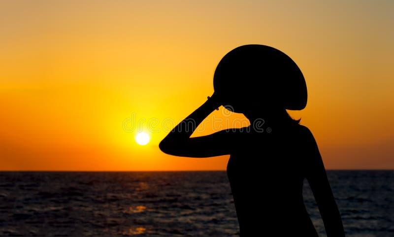 Σκιαγραφία LIT μιας γυναίκας στο καπέλο στο ζωηρόχρωμο και ζωηρό υπόβαθρο ηλιοβασιλέματος στοκ εικόνες