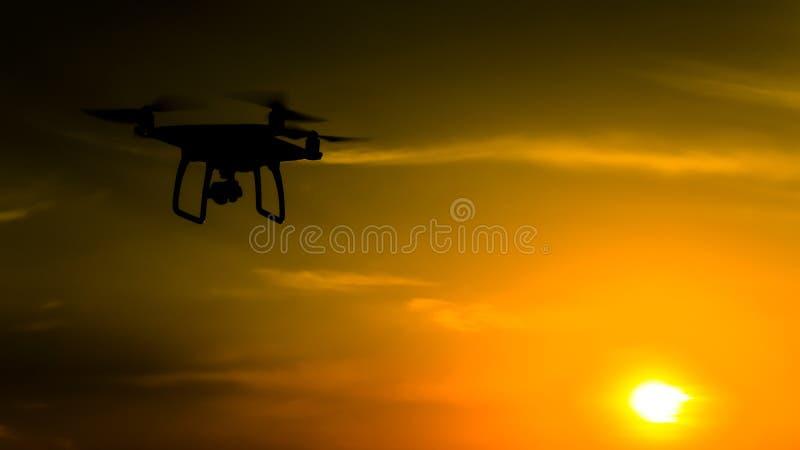 Σκιαγραφία Quadrocopters στα πλαίσια του ηλιοβασιλέματος Πετώντας κηφήνες στοκ εικόνες με δικαίωμα ελεύθερης χρήσης