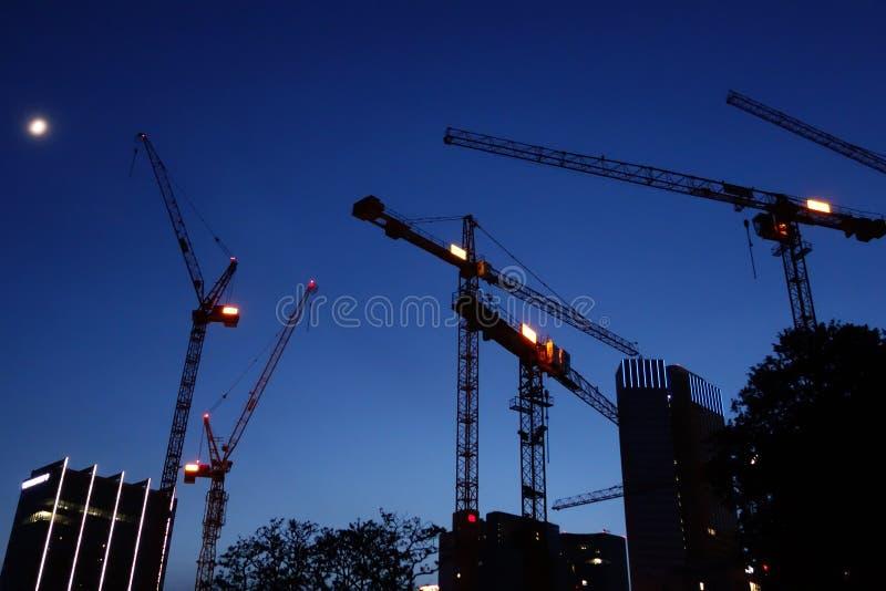 Σκιαγραφίες γερανών τη νύχτα, εργοτάξιο οικοδομής στοκ φωτογραφίες