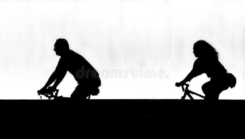 Σκιαγραφίες δύο ανθρώπων που οδηγούν τα ποδήλατα στη νύχτα, στη θαμπάδα κινήσεων στοκ εικόνα με δικαίωμα ελεύθερης χρήσης