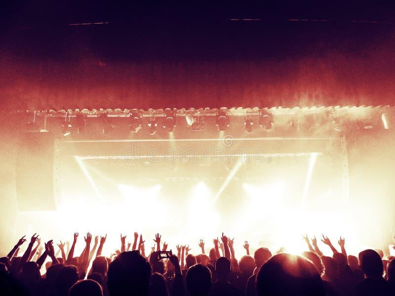 Σκιαγραφίες πλήθους συναυλίας μπροστά από μια φωτεινή σκηνή στοκ φωτογραφία