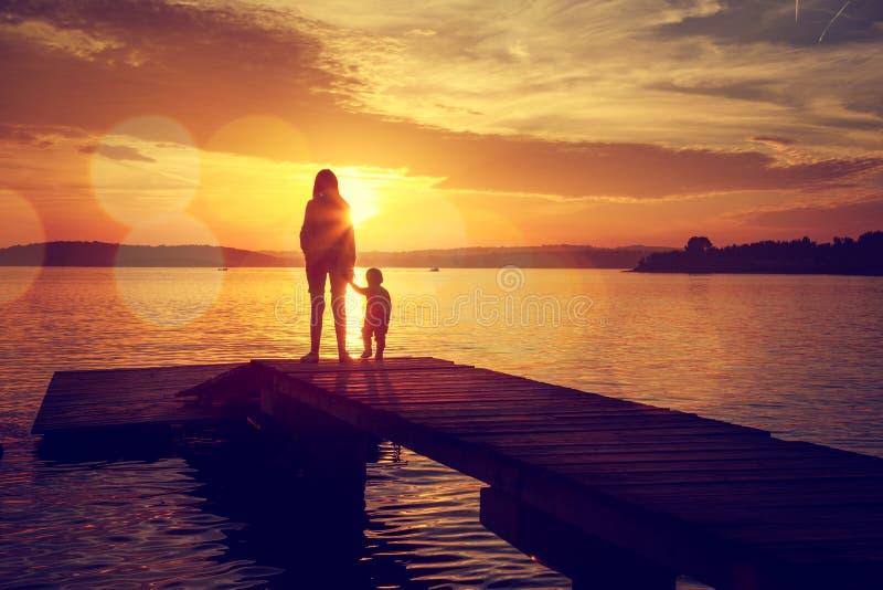 Σκιαγραφίες της μητέρας και του γιου της από τη λίμνη στοκ εικόνες