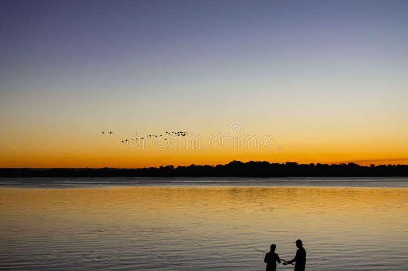 Σκιαγραφίες του άνδρα και της γυναίκας που αλιεύουν με το ηλιοβασίλεμα που απεικονίζει στο νερό και το κοπάδι των πουλιών που πετ στοκ φωτογραφία με δικαίωμα ελεύθερης χρήσης