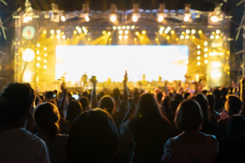 Σκιαγραφίες του πλήθους, ομάδα ανθρώπων, ενθαρρυντική στη συναυλία ζωντανής μουσικής μπροστά από τα ζωηρόχρωμα φω'τα σκηνών στοκ φωτογραφία