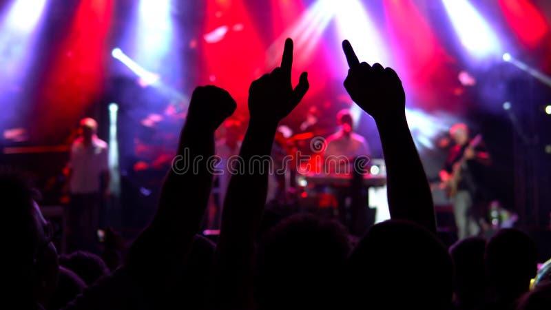 Σκιαγραφίες του πλήθους συναυλίας μπροστά από τα φωτεινά φω'τα σκηνών στοκ εικόνα με δικαίωμα ελεύθερης χρήσης