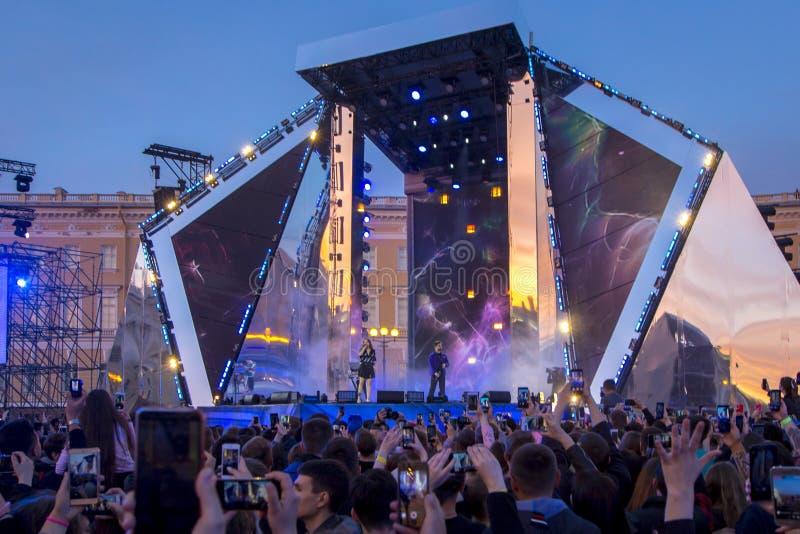 Σκιαγραφίες του πλήθους συναυλίας μπροστά από τα φωτεινά φω'τα σκηνών στοκ εικόνες