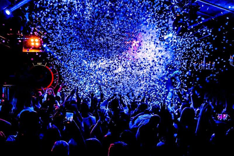 Σκιαγραφίες του πλήθους συναυλίας μπροστά από τα φωτεινά φω'τα σκηνών με το κομφετί στοκ φωτογραφίες