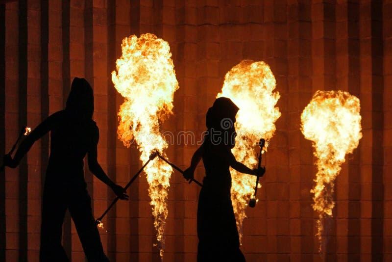 Σκιαγραφίες των ανδρών και των γυναικών στο υπόβαθρο ενός τοίχου πετρών και καίγοντας φανών στοκ φωτογραφία