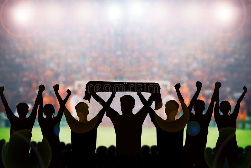 σκιαγραφίες των ανεμιστήρων ποδοσφαίρου σε μια αντιστοιχία και των θεατών στο ποδόσφαιρο στοκ εικόνα