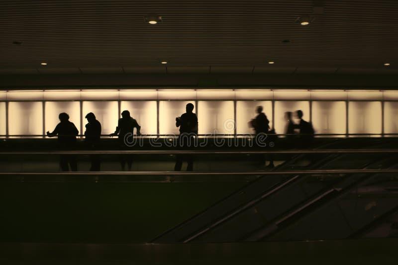 Σκιαγραφίες των ανθρώπων αναδρομικά φωτισμένων σε έναν σκοτεινό σταθμό μετρό στοκ εικόνα