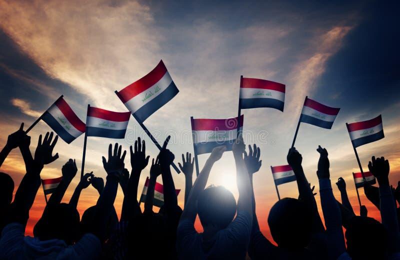 Σκιαγραφίες των ανθρώπων που κυματίζουν τη σημαία του Ιράκ στοκ φωτογραφία