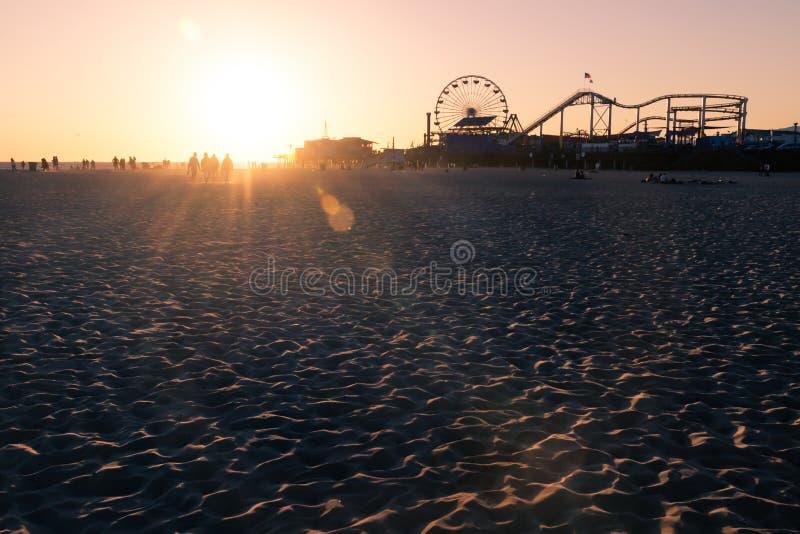 Σκιαγραφίες των ανθρώπων που περπατούν κατά μήκος της παραλίας της Σάντα Μόνικα και του λούνα παρκ στο ηλιοβασίλεμα, Λος Άντζελες στοκ φωτογραφία με δικαίωμα ελεύθερης χρήσης