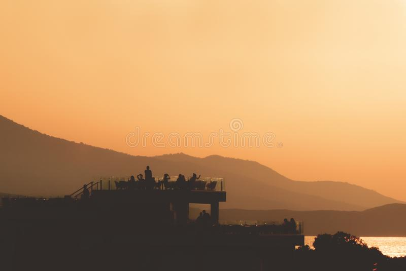 Σκιαγραφίες των ανθρώπων που σε μια στέγη στο ηλιοβασίλεμα στοκ εικόνα