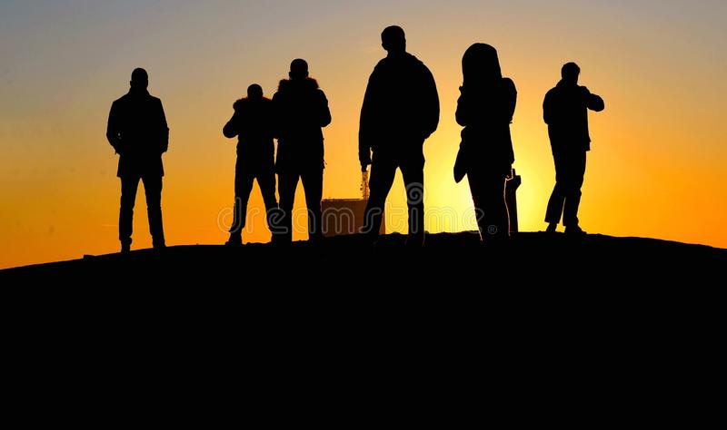 Σκιαγραφίες των ανθρώπων στο θερμό ζωηρόχρωμο ηλιοβασίλεμα σε Βελιγράδι, Σερβία στοκ φωτογραφίες