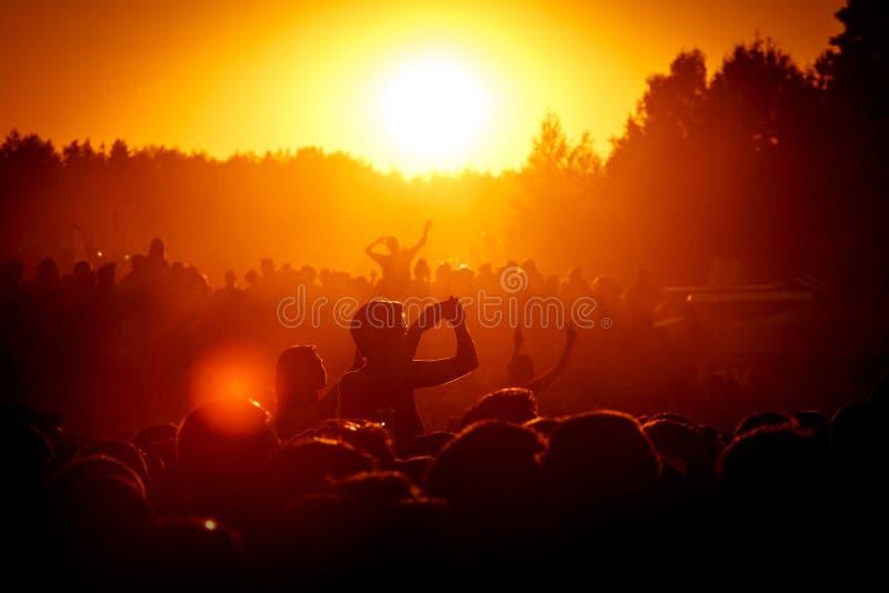 Σκιαγραφίες των ανθρώπων υπαίθρια στο φεστιβάλ μουσικής στοκ εικόνα