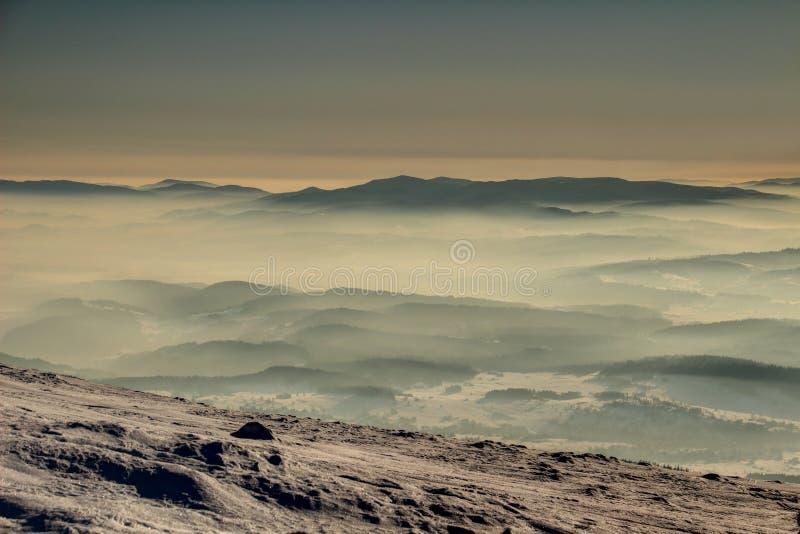 Σκιαγραφίες των βουνών Gorce στη θάλασσα της ομίχλης στην ανατολή Πολωνία στοκ εικόνα