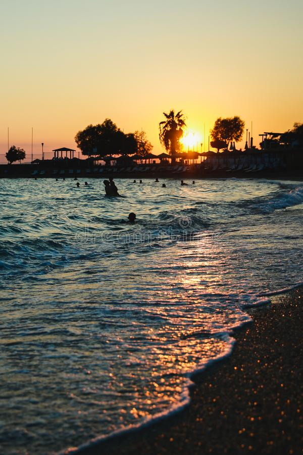 Σκιαγραφίες των ευτυχών ανθρώπων που κολυμπούν και που παίζουν στη θάλασσα στο ηλιοβασίλεμα, έννοια για την κατοχή της διασκέδαση στοκ φωτογραφίες με δικαίωμα ελεύθερης χρήσης