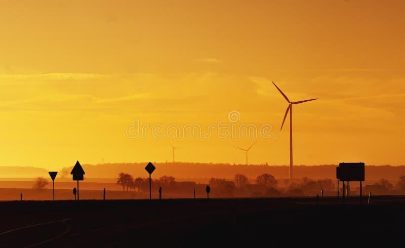 Σκιαγραφίες των σημαδιών κυκλοφορίας και των εγκαταστάσεων αιολικής ενέργειας στο πορτοκαλί φως του ήλιου στοκ φωτογραφίες