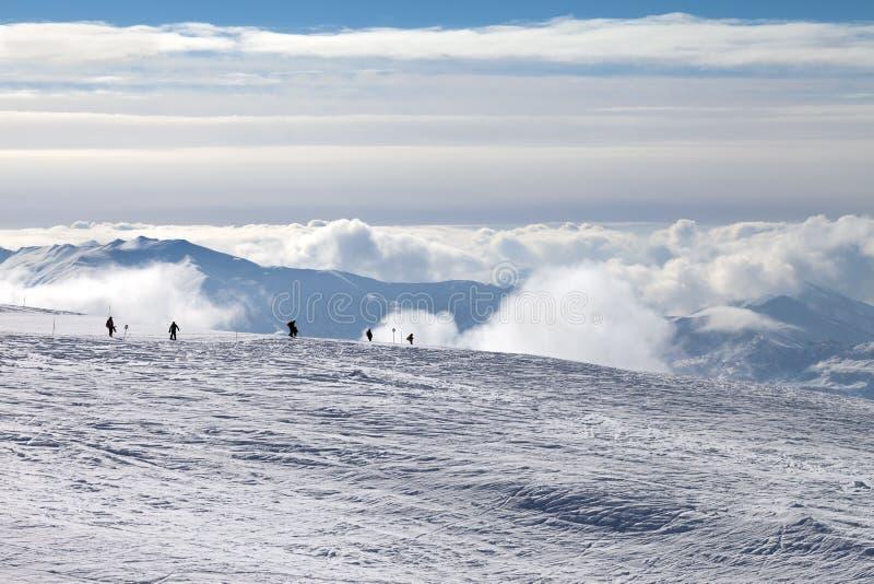 Σκιαγραφίες των σκιέρ και των snowboarders στη χιονώδη κλίση και τα βουνά σκι στοκ φωτογραφίες