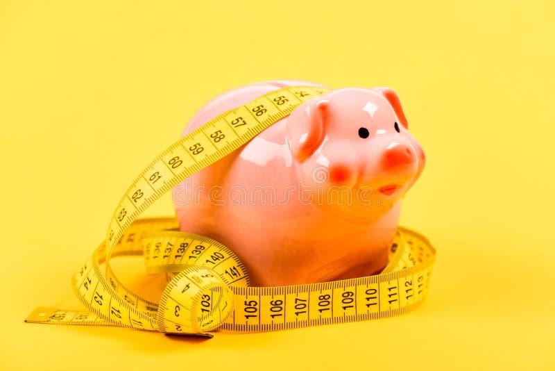 Σκλήρυνση ζωνών Αύξηση οικονομίας και προϋπολογισμών piggy τράπεζα με την ταινία μέτρησης moneybox έννοια δανείου Πάρτε την πίστω στοκ φωτογραφία