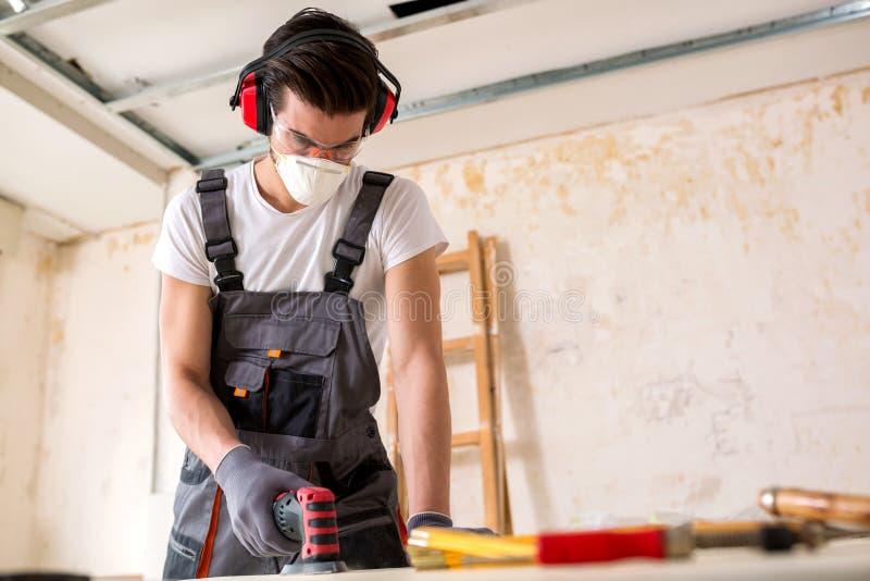 Σκληρά εργαζόμενος νεαρός άνδρας που εφαρμόζει τις τελευταίες πινελιές στοκ φωτογραφία με δικαίωμα ελεύθερης χρήσης