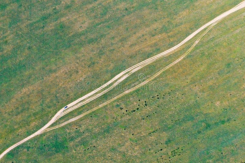 Σκονισμένος δρόμος ρύπου χώρας και διάβαση του αυτοκινήτου σε το στοκ φωτογραφία