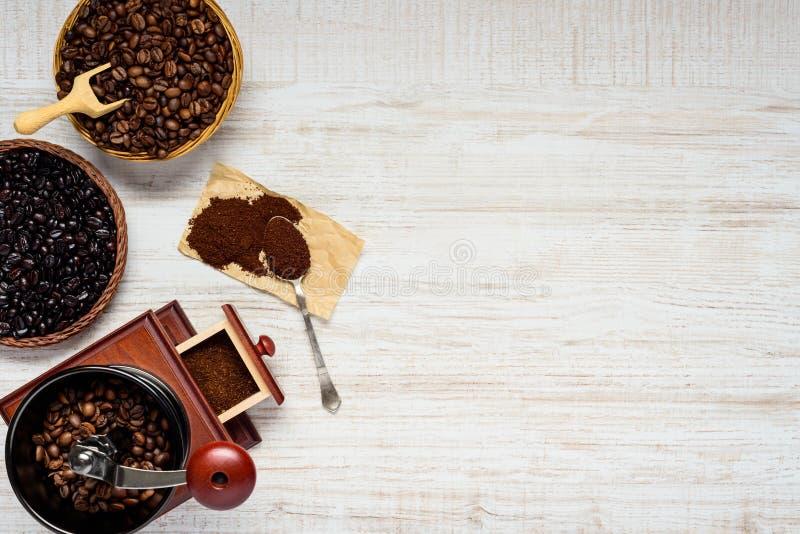 Σκοτεινά και καφετιά φασόλια καφέ με το μύλο στο διάστημα αντιγράφων στοκ εικόνα