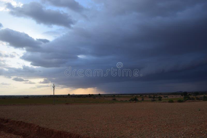 Σκοτεινά μαύρα σύννεφα σχετικά με το έδαφος στοκ εικόνα