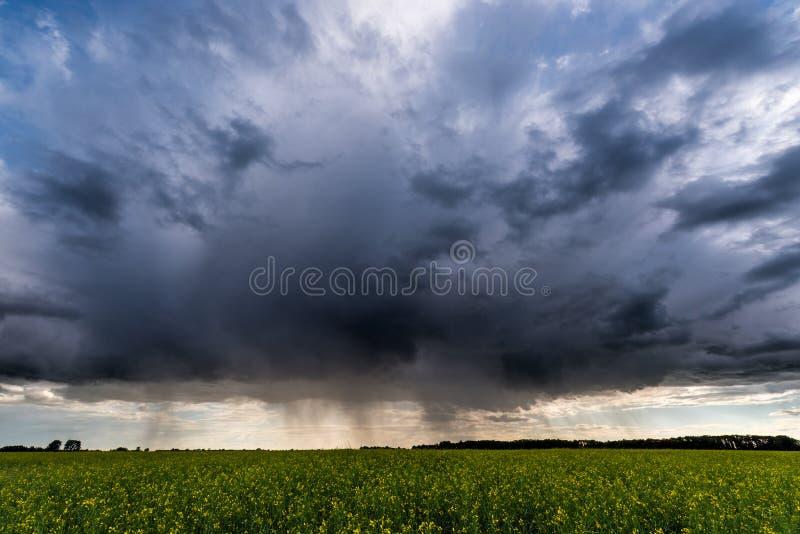 Σκοτεινά σύννεφα βροχής επάνω από τον τομέα βιασμών, στοκ φωτογραφίες