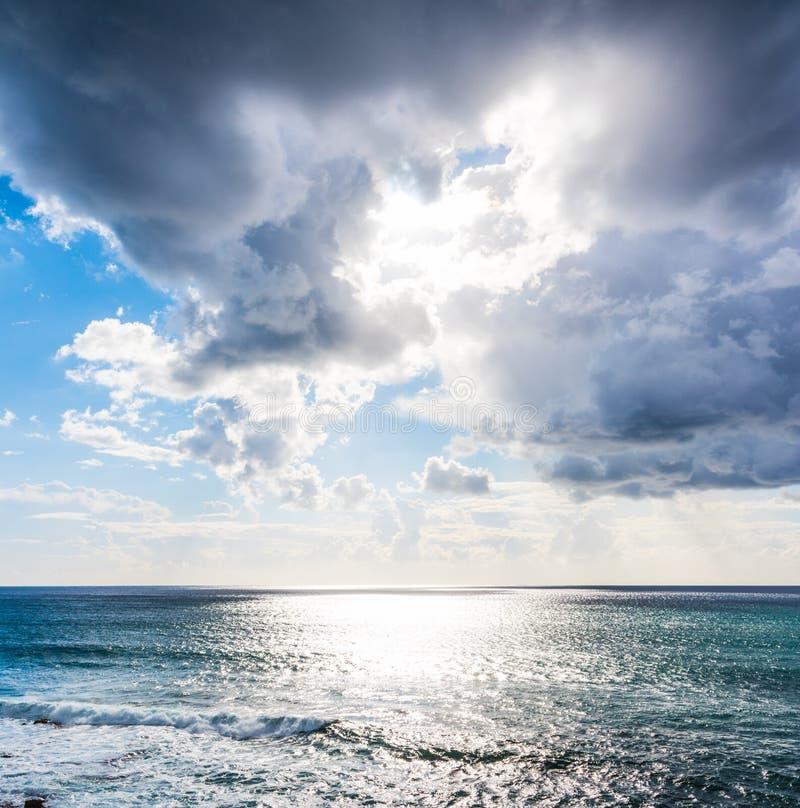 Σκοτεινά σύννεφα και λάμποντας ήλιος πέρα από τη θάλασσα στοκ εικόνα