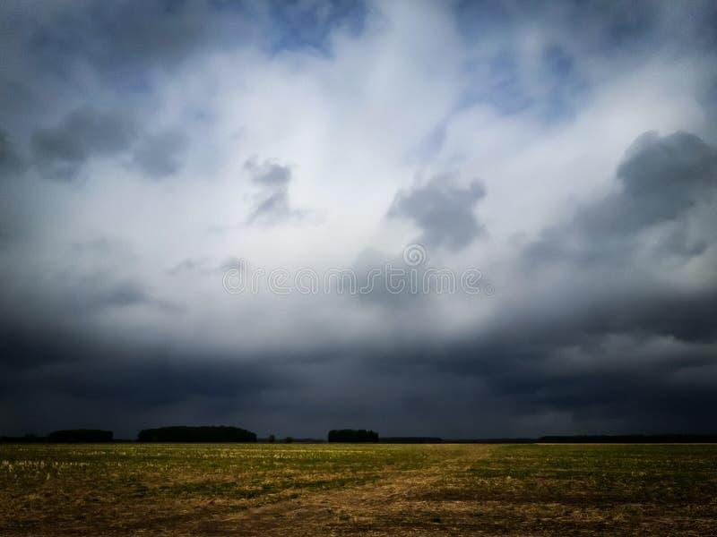 Σκοτεινά σύννεφα ουρανού στον τομέα στοκ φωτογραφίες