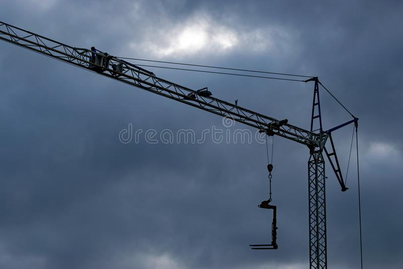 Σκοτεινά σύννεφα πέρα από έναν γερανό κατασκευής στοκ εικόνα