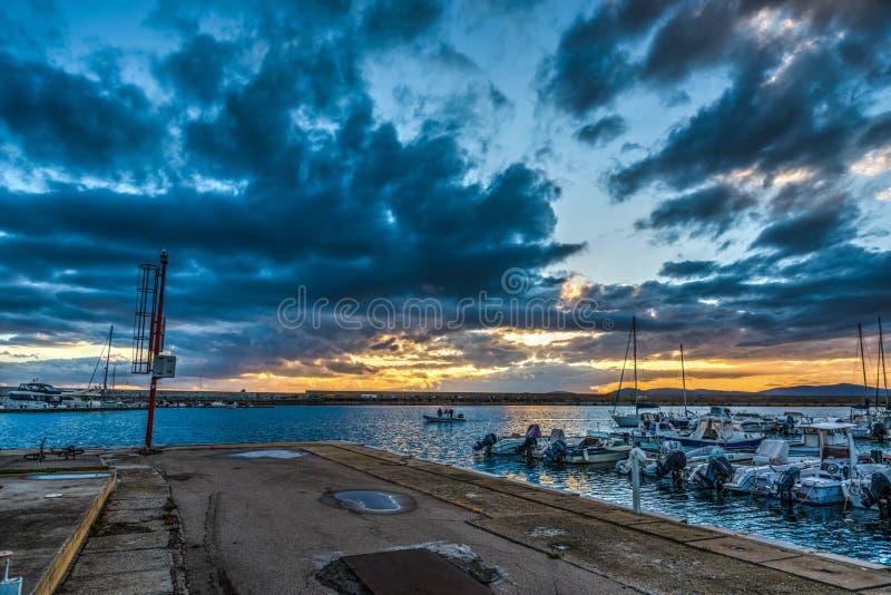 Σκοτεινά σύννεφα πέρα από το λιμάνι Alghero στο ηλιοβασίλεμα στοκ φωτογραφία με δικαίωμα ελεύθερης χρήσης