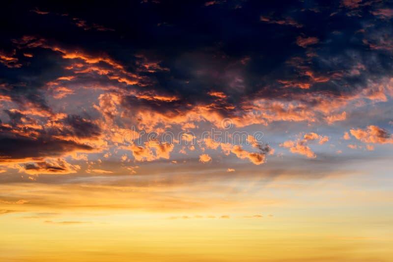 Σκοτεινά thunderclouds με τις κόκκινες πορτοκαλιές αντανακλάσεις του ήλιου ρύθμισης Φυσικά σύννεφα θύελλας αναμμένα από τις τελευ στοκ εικόνα