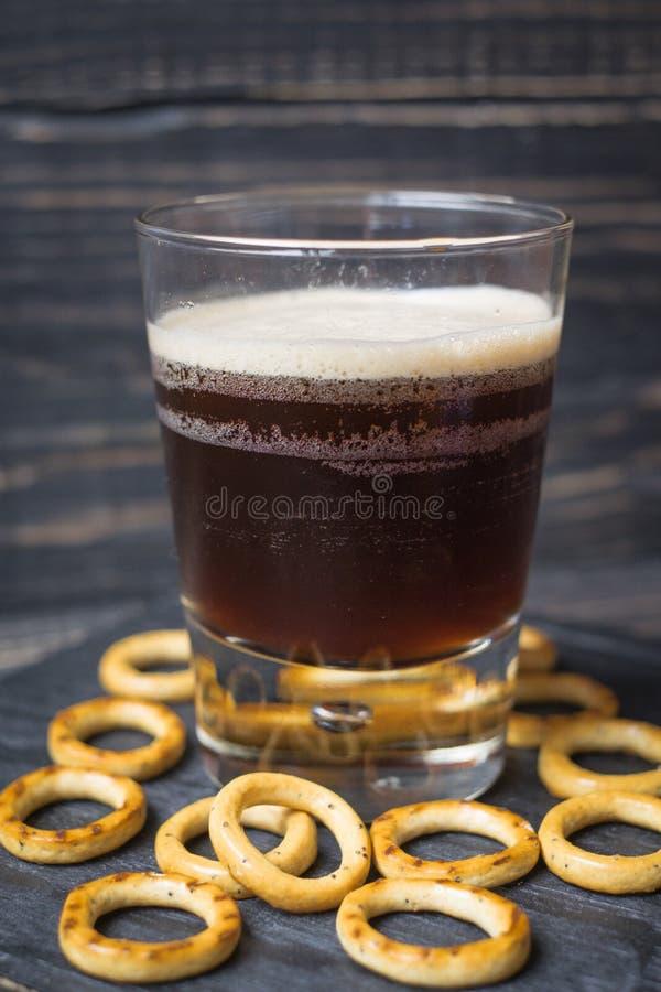 Σκοτεινή μπύρα σε ένα γυαλί σε ένα ξύλινο υπόβαθρο στοκ φωτογραφία με δικαίωμα ελεύθερης χρήσης