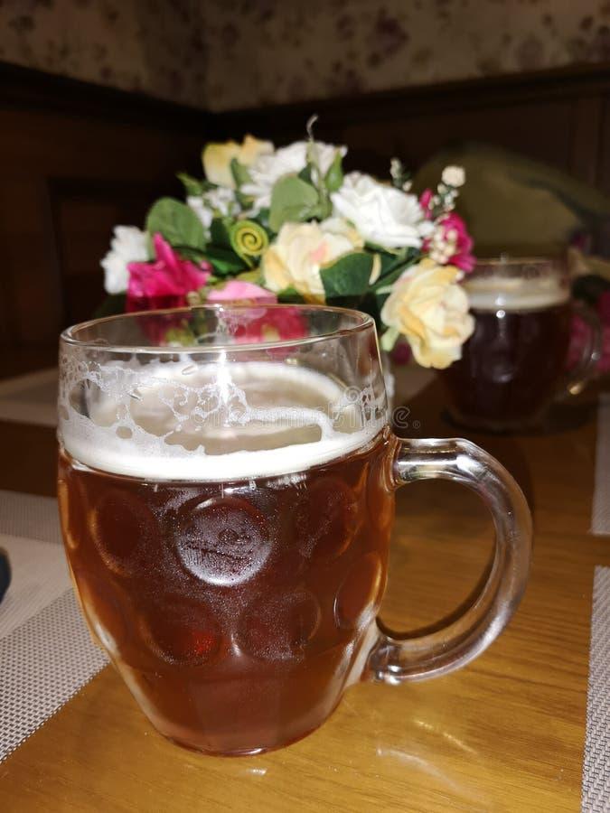 Σκοτεινή μπύρα σε μια κούπα σε έναν πίνακα σε ένα υπόβαθρο των λουλουδιών στοκ φωτογραφία με δικαίωμα ελεύθερης χρήσης