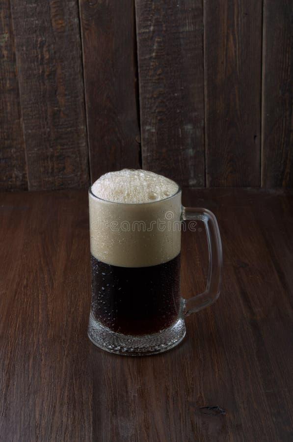 Σκοτεινή μπύρα στο καφετί ξύλινο υπόβαθρο στοκ φωτογραφίες
