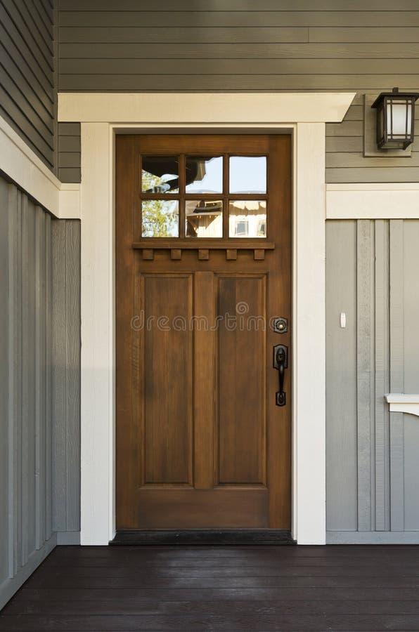 Σκοτεινή ξύλινη μπροστινή πόρτα ενός σπιτιού στοκ εικόνες