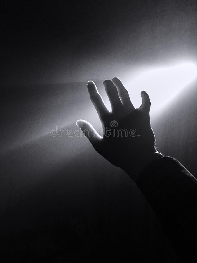 σκοτεινή σκιαγραφία του ανθρώπινου αρσενικού χεριού με τα δάχτυλα στο επίκεντρο ή backlight το φως με τη χειρονομία στο μαύρο υπό στοκ φωτογραφία με δικαίωμα ελεύθερης χρήσης
