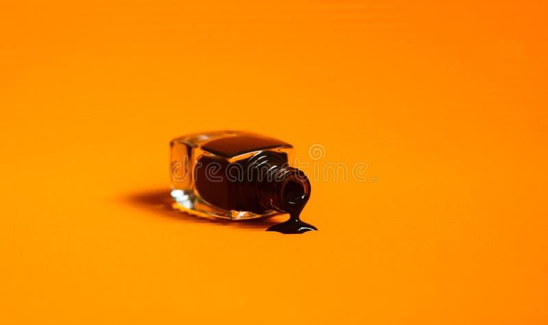 Σκοτεινή στιλβωτική ουσία καρφιών που ανατρέπεται από το μπουκάλι Δονούμενο πορτοκαλί υπόβαθρο στοκ εικόνα