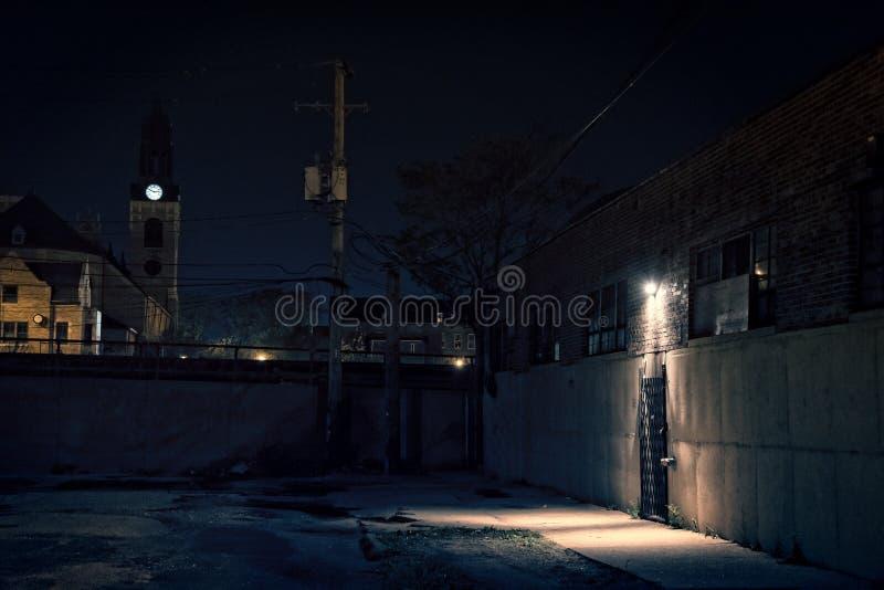 Σκοτεινή τρομακτική αλέα τη νύχτα με την είσοδο αποθηκών εμπορευμάτων στοκ φωτογραφία με δικαίωμα ελεύθερης χρήσης