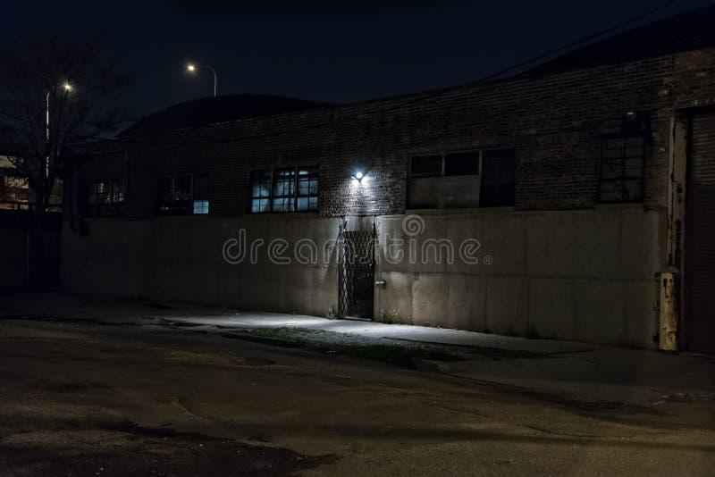 Σκοτεινή τρομακτική αλέα τη νύχτα με την περιορισμένη είσοδο αποθηκών εμπορευμάτων πορτών στοκ εικόνες